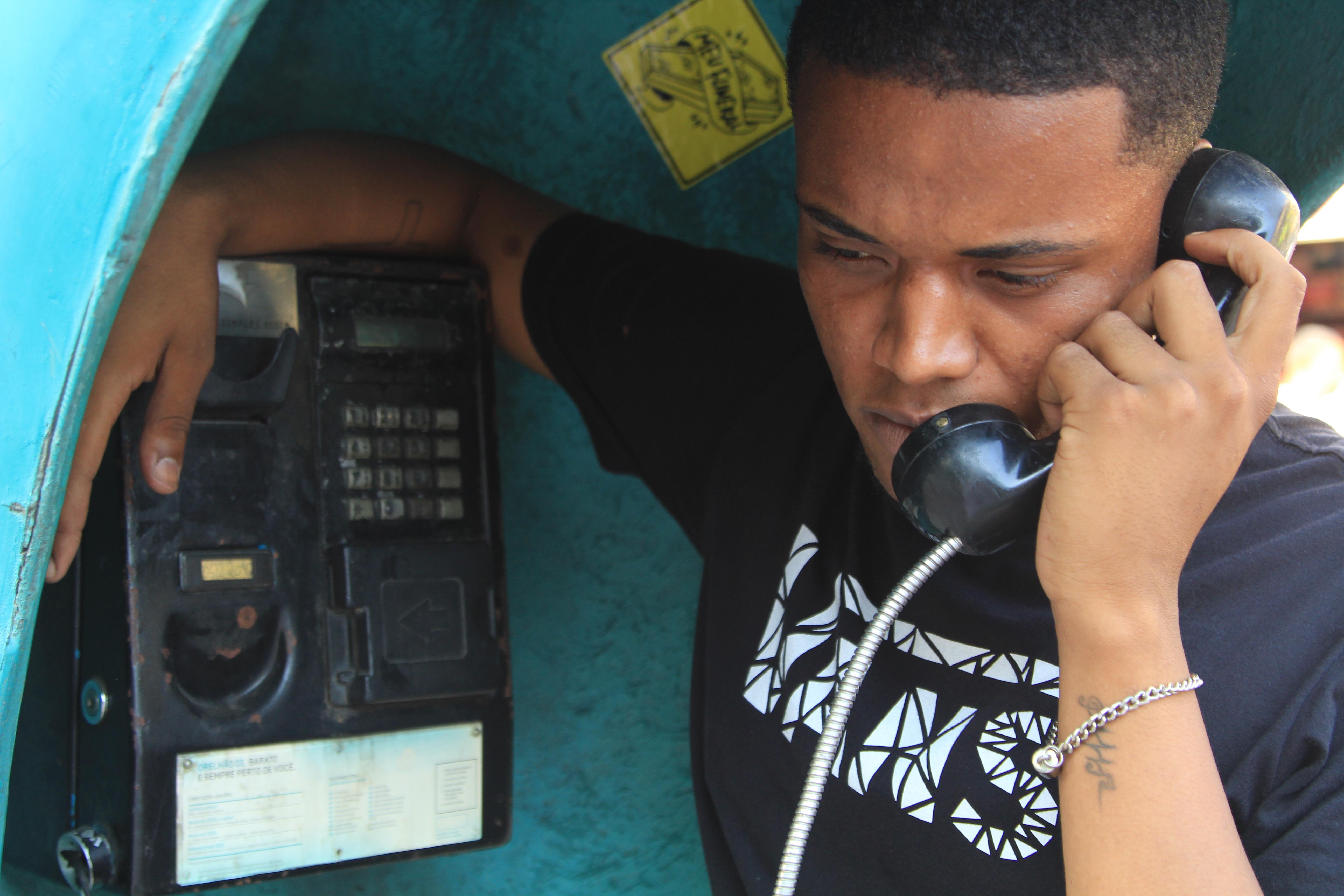 Jovem Negro no orelhão telefone público campanha emprego QUalPerfil# racismo